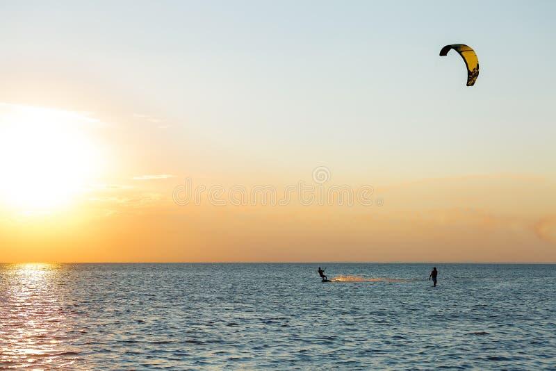 Kiter profesional que hace un truco complicado en un fondo hermoso de la puesta del sol imagen de archivo