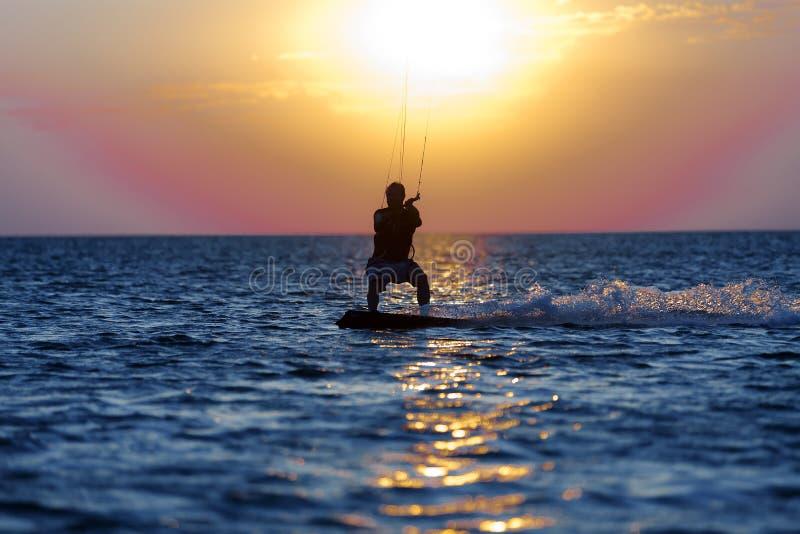 Kiter profesional que hace un truco complicado en un fondo hermoso de la puesta del sol imagen de archivo libre de regalías