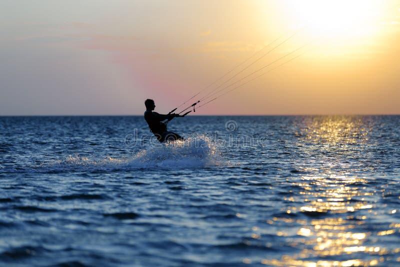 Kiter profesional que hace un truco complicado en un fondo hermoso de la puesta del sol foto de archivo libre de regalías