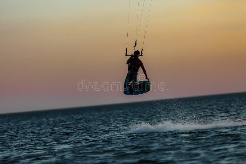 Kiter profesional que hace un truco complicado en un fondo hermoso de la puesta del sol fotografía de archivo