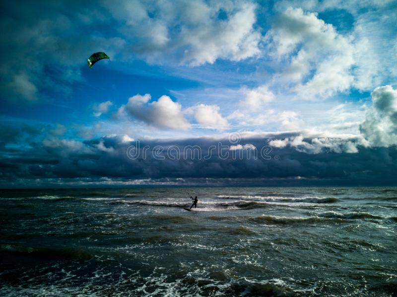 Kiter in storm. Hardihood kiter in the approaching heavy storm. Dangerous adventure stock photography