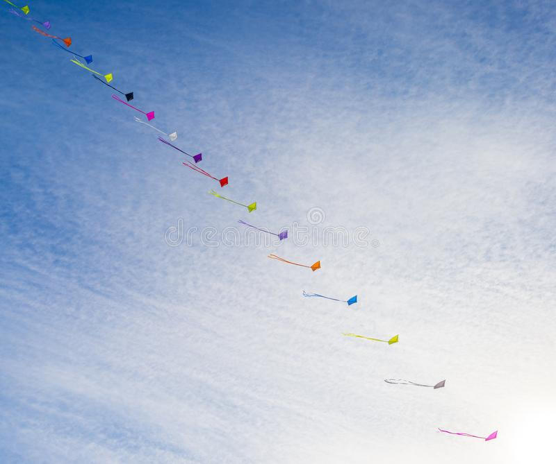 Kites flying in the wind in a blue sky in sunlight at fall stock photo