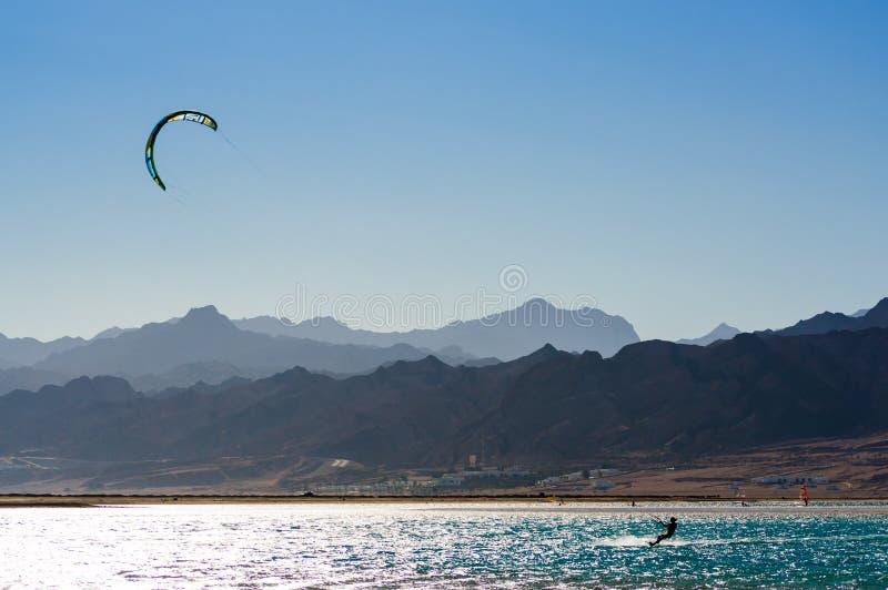 Kitesurfer едет в Красном Море на предпосылке скалистого побережья в Египте Dahab южном Синай стоковая фотография rf