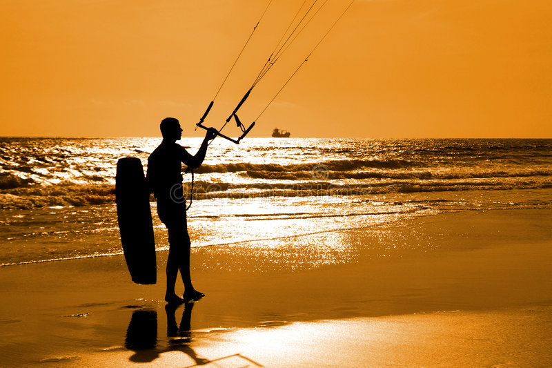 Kitesurfer. Silhouette moving on the sand an holding equipment royalty free stock photography