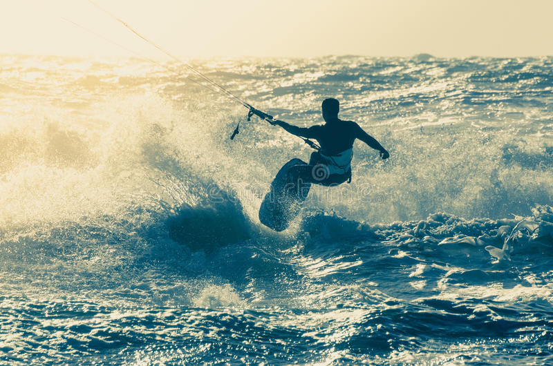 Kitesurfer. In action on a beautiful background of spray during the sunset royalty free stock photo