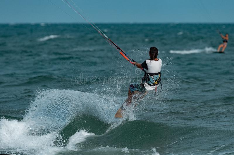 Kitesurfer In Action. Kitesurfing on the waves of the sea in Mui Ne beach, Phan Thiet, Binh Thuan, Vietnam. Kitesurfing, Kiteboarding action photos Kitesurfer In stock photo
