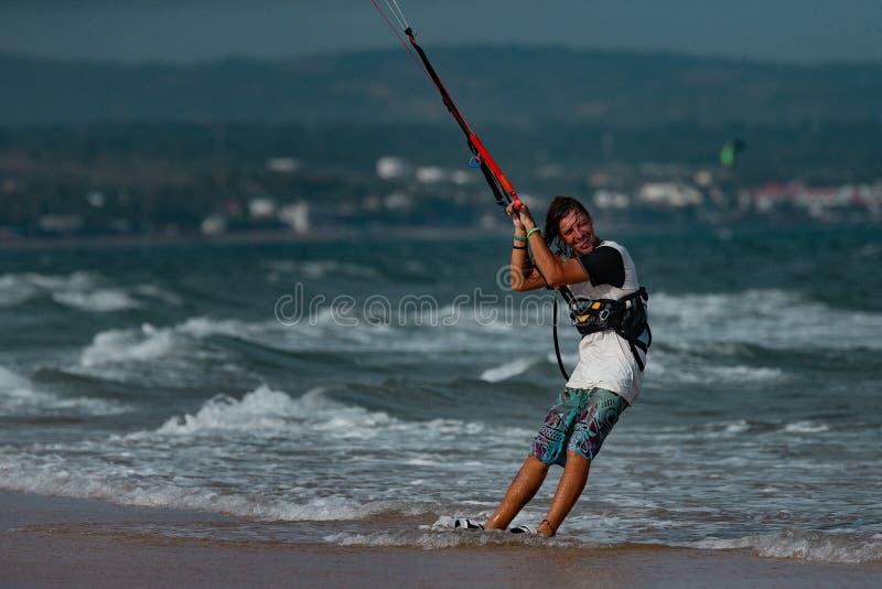 Kitesurfer In Action. Kitesurfing on the waves of the sea in Mui Ne beach, Phan Thiet, Binh Thuan, Vietnam. Kitesurfing, Kiteboarding action photosKitesurfer In stock photo