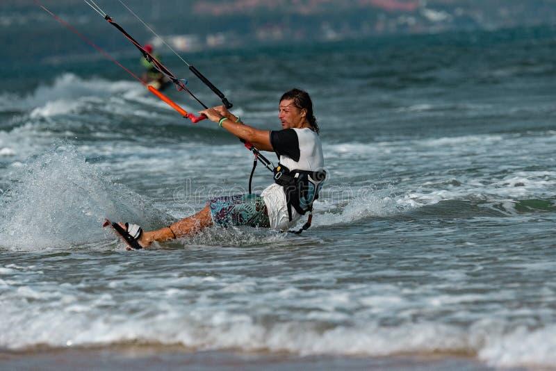 Kitesurfer In Action. Kitesurfing on the waves of the sea in Mui Ne beach, Phan Thiet, Binh Thuan, Vietnam. Kitesurfing, Kiteboarding action photosKitesurfer In royalty free stock images