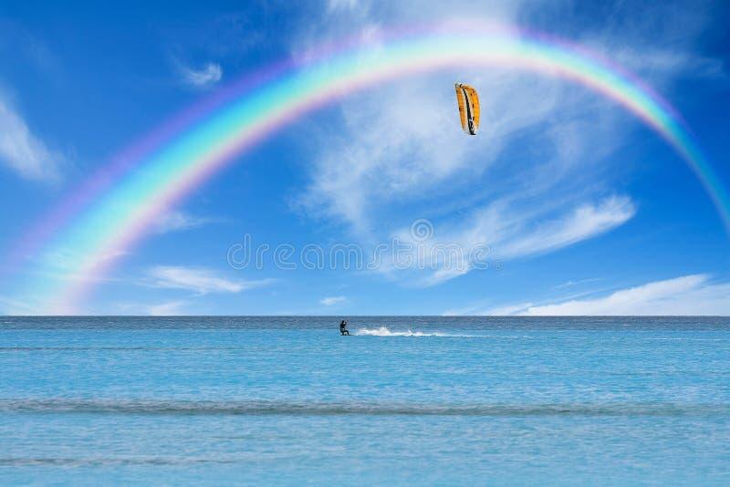 Kitesurfer in der Aktion auf klarem blauem Wasser unter einem Regenbogen lizenzfreies stockfoto