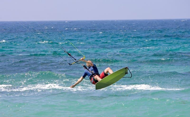 Kitesurfer die door de lucht op een zonnig strand vliegt stock afbeelding