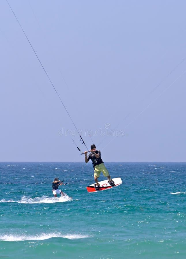 Kitesurfer die door de lucht op een zonnig strand vliegt stock fotografie