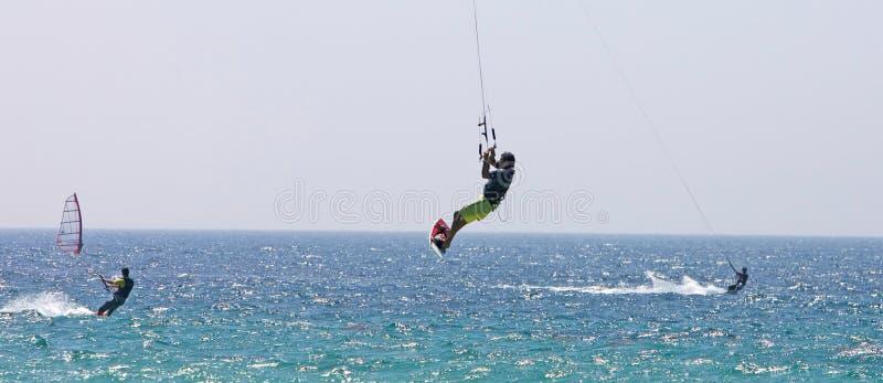 Kitesurfer die door de lucht op een zonnig strand vliegt stock foto's