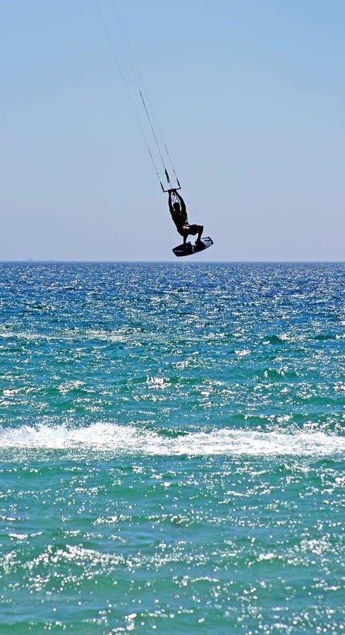 Kitesurfer die hoog door de lucht als zijn vlieger vliegt raakt wat ernstige wind. stock fotografie