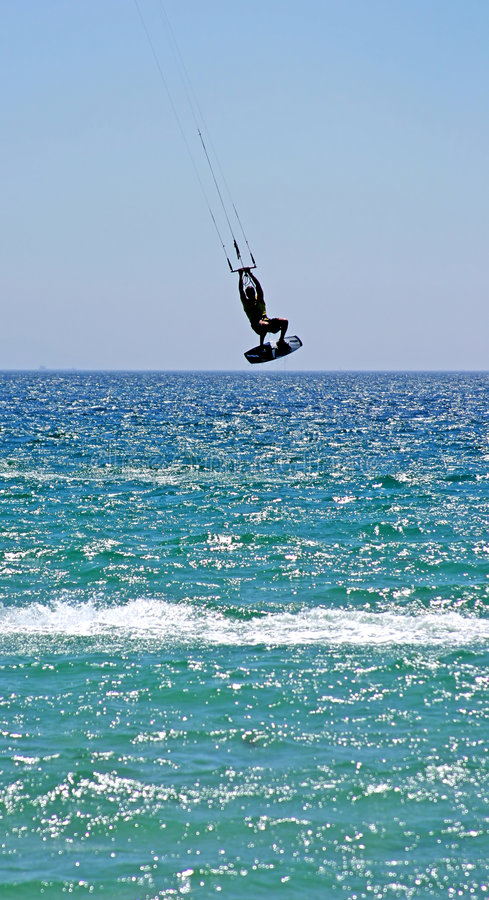 Kitesurfer flying high through the air as his kite hits some serious wind. stock photography