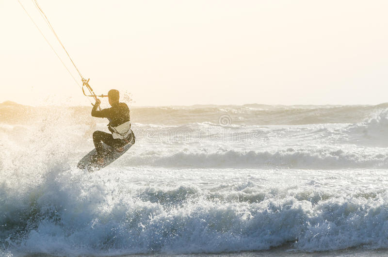 Kitesurfer. Jumping on a beautiful background of spray during the sunset stock photo