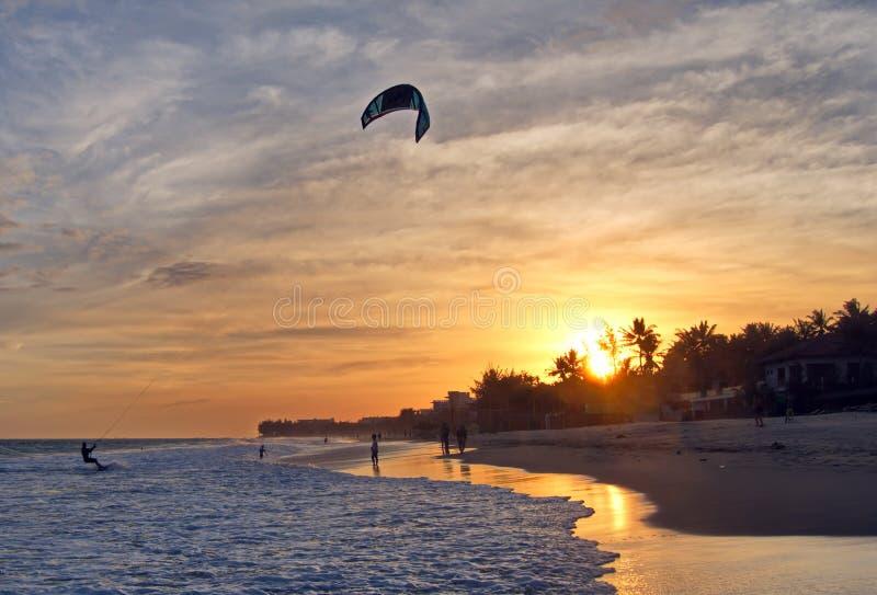 Kitesurfer kiteboarder kitesurfing kiteboarding at sunset. Sunset kite ride in Mui Ne kite spot beach, Vietnam royalty free stock photo