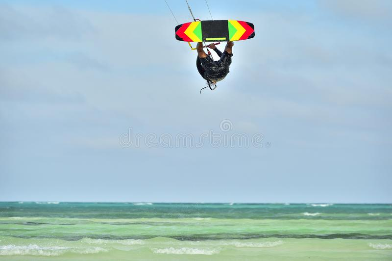 A kitesurfer performing an aerial trick. stock image