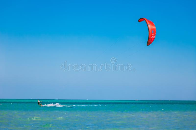 Kitesurfer with red kite gliding over the Red sea. stock photos