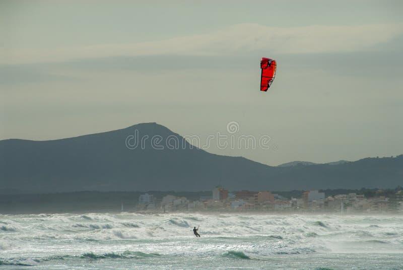 Kitesurfer surfa com um papagaio vermelho na praia de Mallorca foto de stock royalty free