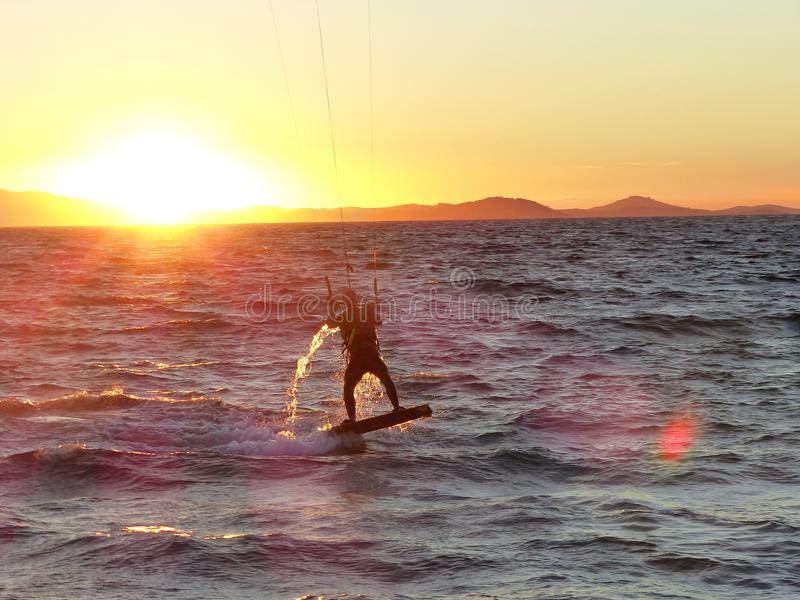 Kitesurfer surfs and jumps into sunset in Hyeres , France royalty free stock image