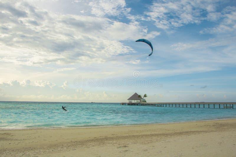 A kitesurfer surfs near the beach near a resort in Maldives stock photo