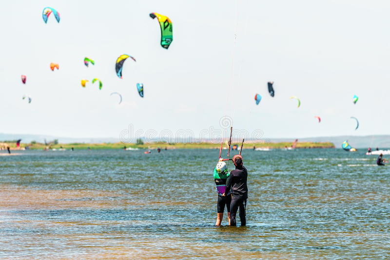 Kitesurfer trainer at sunny Black Sea Blaga Beach resort trains woman in kitesurfing standing in calm shallow waters of firth on d. Istant flying kites royalty free stock photos