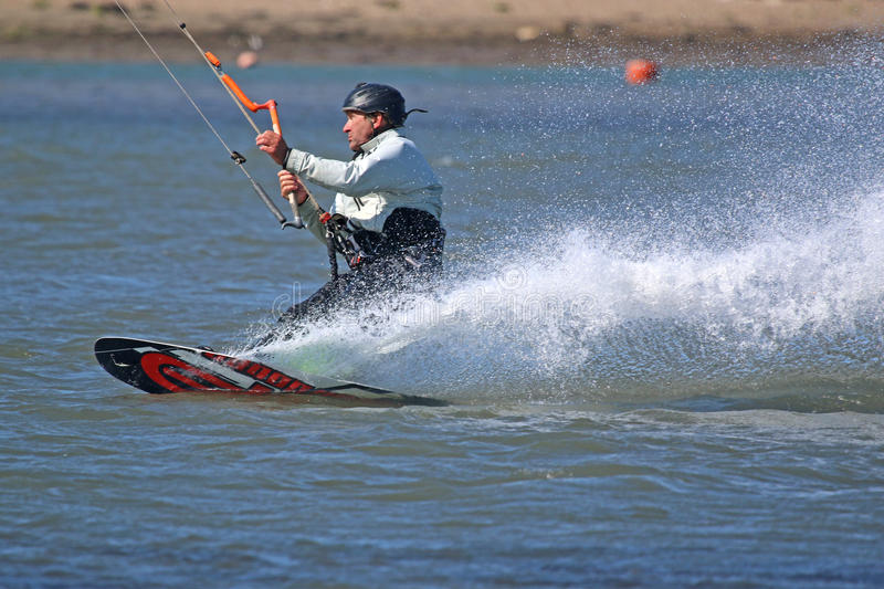 Kitesurfers carving his board. Kitesurfer riding on his board edge royalty free stock images