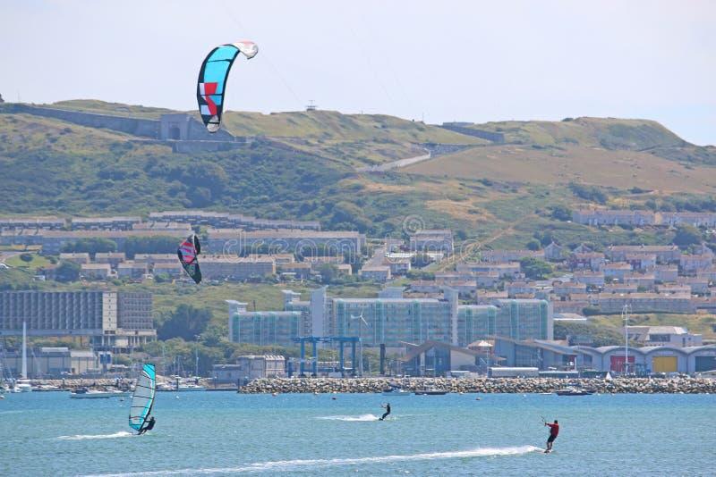 Kitesurfers i den Portland hamnen, Dorset royaltyfria bilder