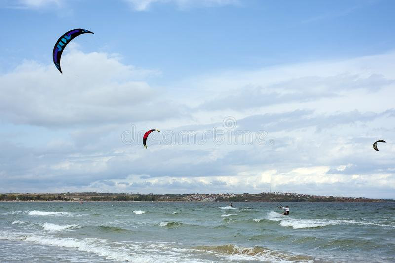Kitesurfers ride kites on Black Sea at sandy beach in Bulgaria, Sozopol on sunny day at sunset on blue sky and clouds background. royalty free stock images