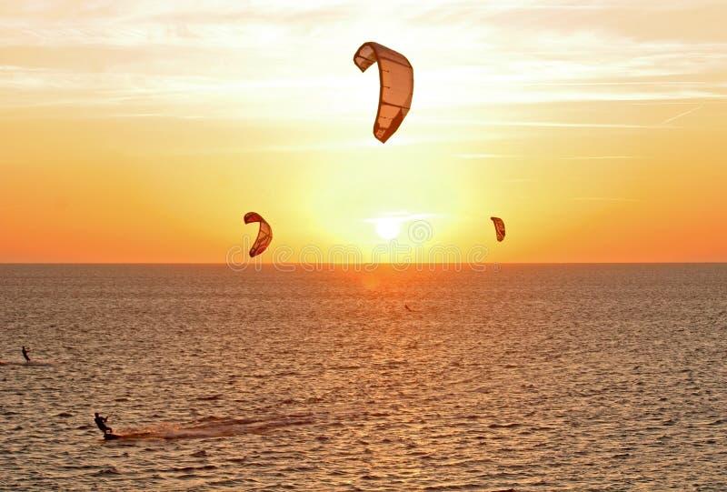 Kitesurfers am Sonnenuntergang lizenzfreies stockfoto