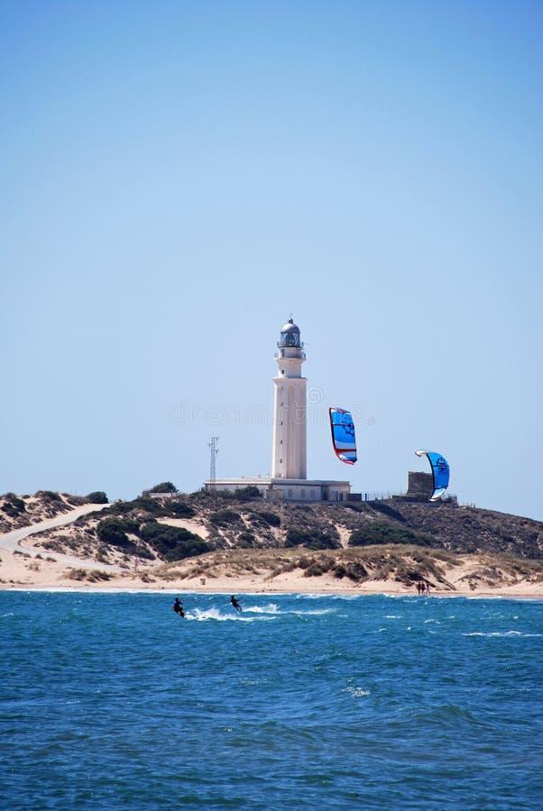 Kitesurfers und Leuchtturm bei Kap Trafalgar, Spanien lizenzfreie stockfotografie