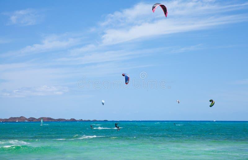 Kitesurfing. Fuerteventura,Spain - May, 2012: Practicing kitesurfing (kiteboarding) at the Corralejo Flag Beach on Fuerteventura, Canary Islands. Strong winds royalty free stock photos