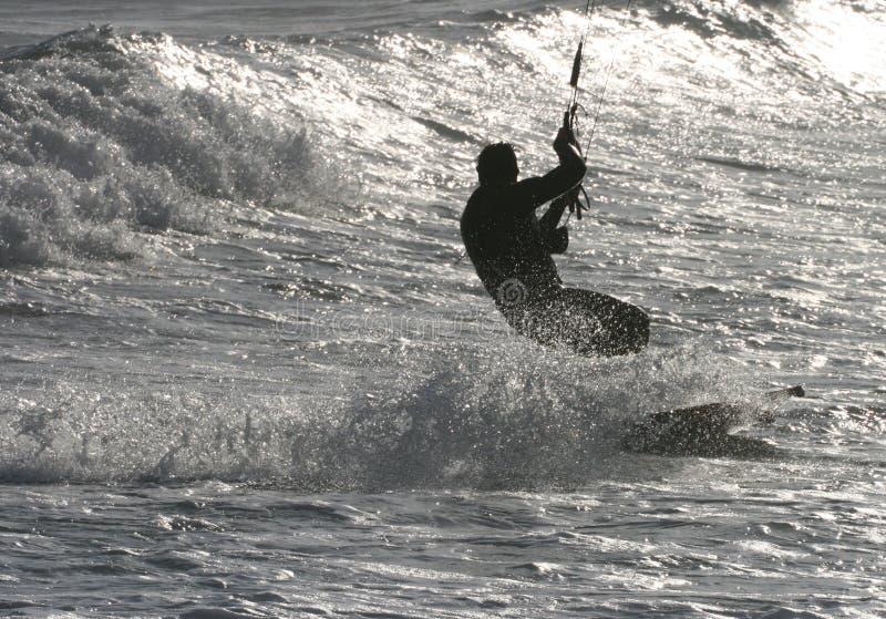 Kitesurfing auf funkelndem Meer lizenzfreie stockbilder