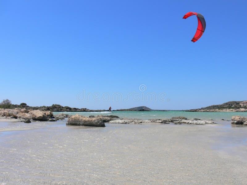 Kitesurfing em volta das rochas fotos de stock