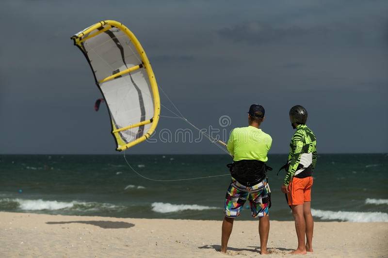 Kitesurfing instruction. Kitesurfing instructor and male student in sea waters men trying to lift kite royalty free stock image