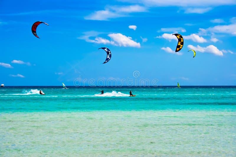 Kitesurfing in Italy. Kitesurfers gliding at high speed around the beach Cinta, Sardinia royalty free stock images