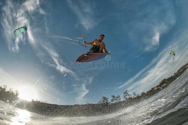 Kitesurfing. Kiteboarding action photos man among waves quickly goes stock photo