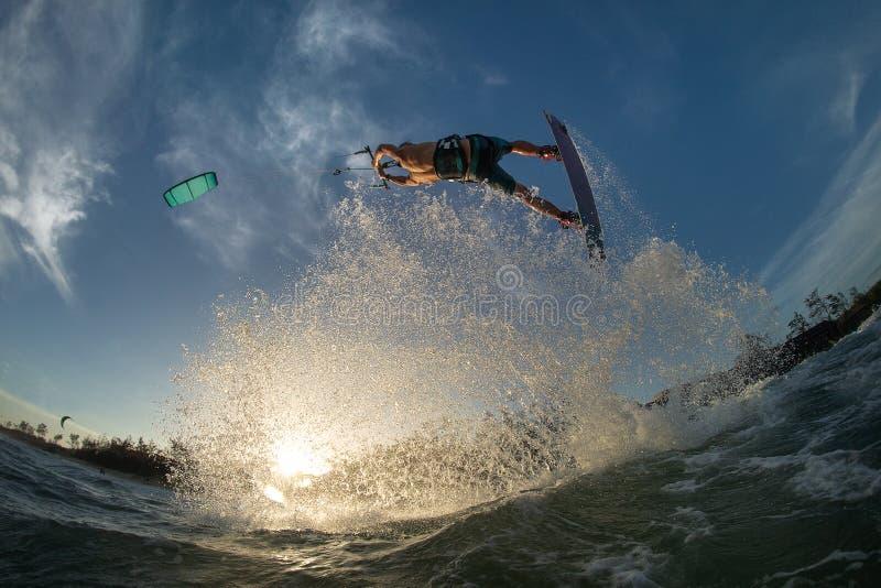 Kitesurfing. Kiteboarding action photos man among waves quickly goes royalty free stock photo