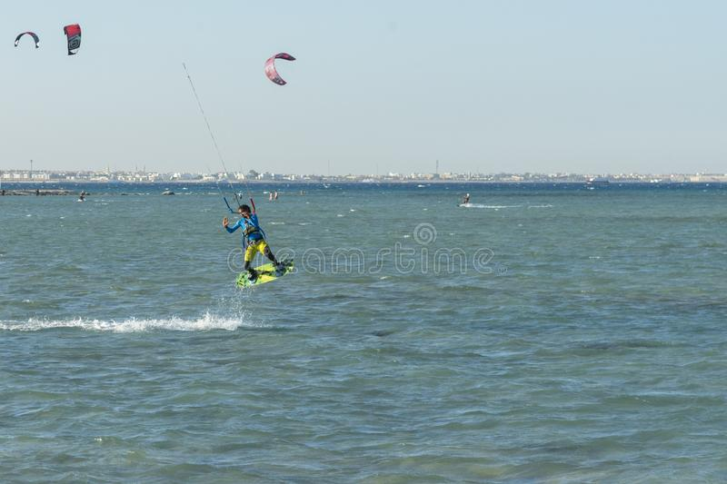 Kitesurfing Kiteboarding action photos man among waves quickly goes. A kite surfer rides the waves. lens illumination. toned.  stock photos
