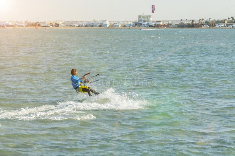 Kitesurfing Kiteboarding action photos man among waves quickly goes. A kite surfer rides the waves. lens illumination. toned stock image
