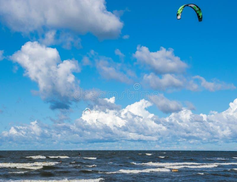 Kitesurfing. Kiteboarding action photos. Man among waves quickly goes stock image