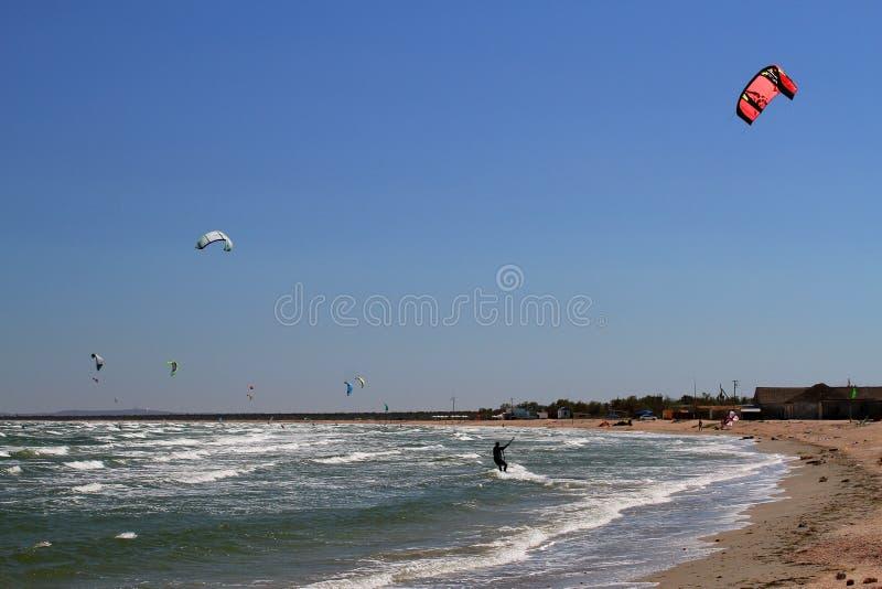 Kitesurfing nas ondas do mar Vista panorâmica do kitesurf praticando dos povos foto de stock