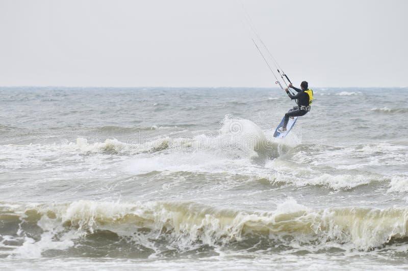 Kitesurfing no pulverizador. imagem de stock
