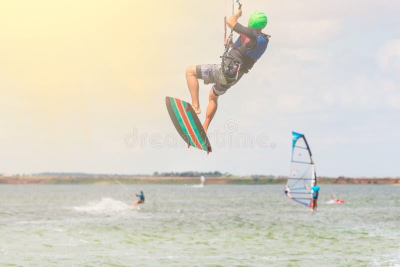 Kitesurfing O homem novo est? voando na onda do mar na placa no dia ensolarado imagem de stock royalty free