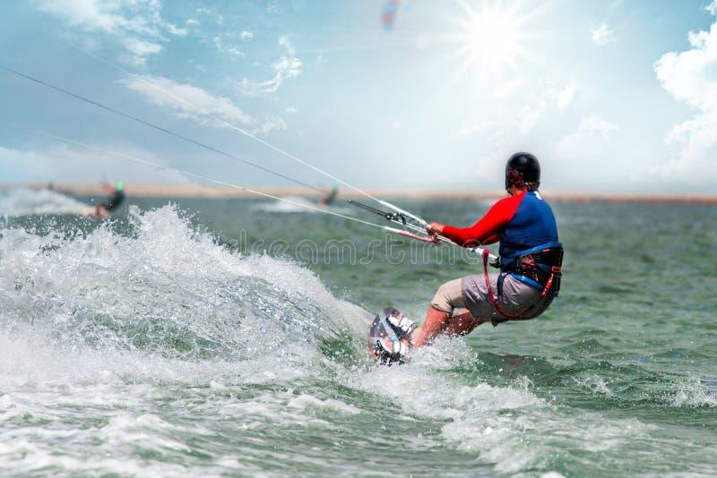 Kitesurfing O homem novo est? voando na onda do mar na placa no dia ensolarado imagem de stock