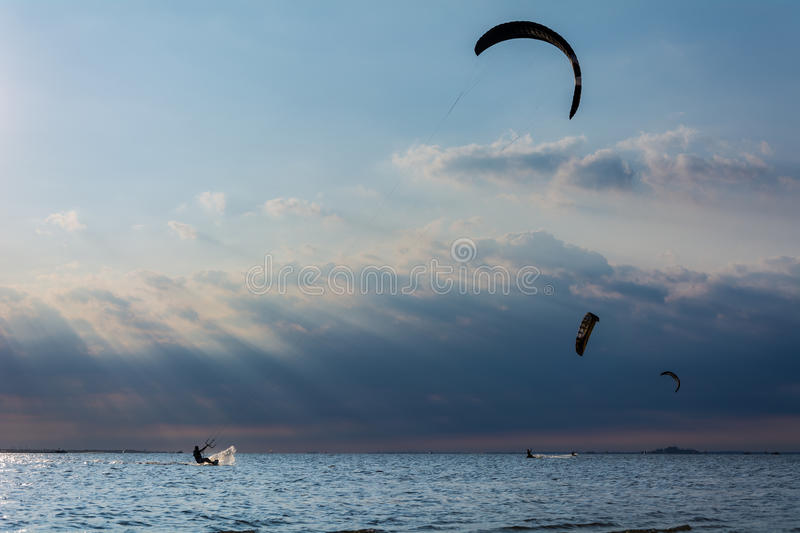Kitesurfing Sandy Hook. Kitesurfers at Sandy Hook Bay with sunbeams stream through clouds over the sky royalty free stock images