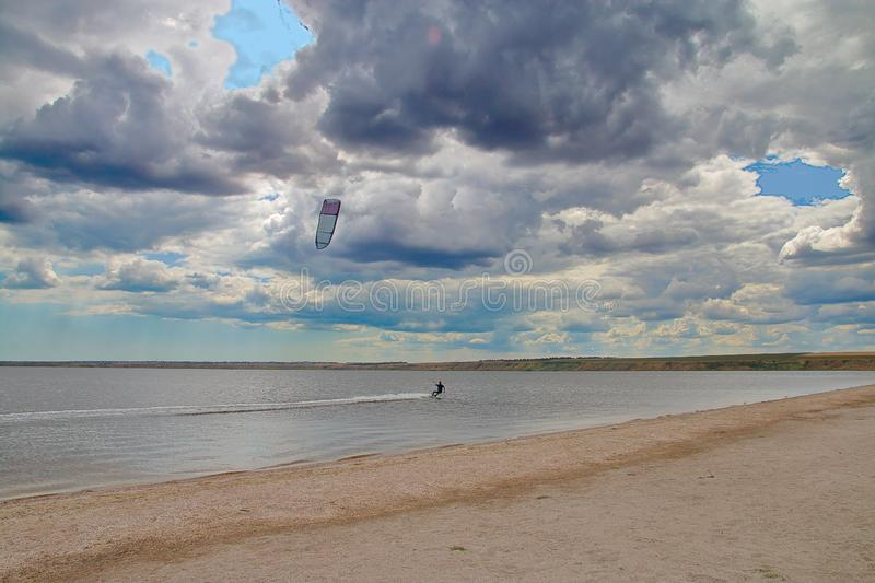 Kitesurfing under a cloudy sky. The photo was taken in Ukraine, on the Tiligulsky estuary. The picture shows a young man kitesurfing under a cloudy sky royalty free stock photography