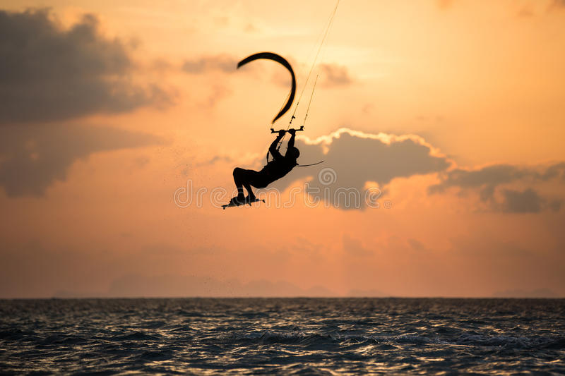 Kitesurfing. Various tricks done by rider on a kiteboard shot at sunset with beautiful backlit royalty free stock photo