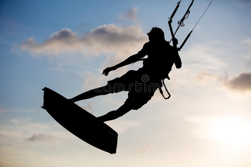 Kitesurfing. Various tricks done by rider on a kiteboard shot at sunset with beautiful backlit stock image