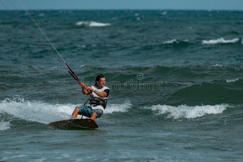 Kitesurfer In Action. Kitesurfing on the waves of the sea in Mui Ne beach, Phan Thiet, Binh Thuan, Vietnam. Kitesurfing, Kiteboarding action photosKitesurfer In stock image